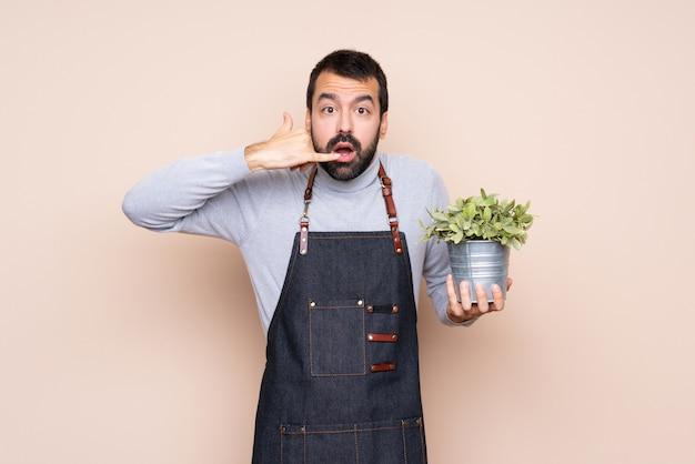 Equipaggi la tenuta della pianta che fa il gesto e il dubbio del telefono