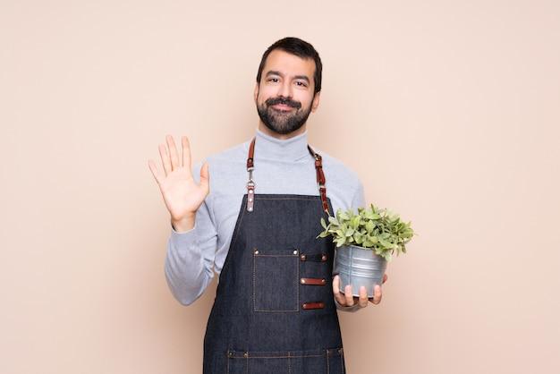 Equipaggi la tenuta della pianta sopra fondo isolato che saluta con la mano con l'espressione felice