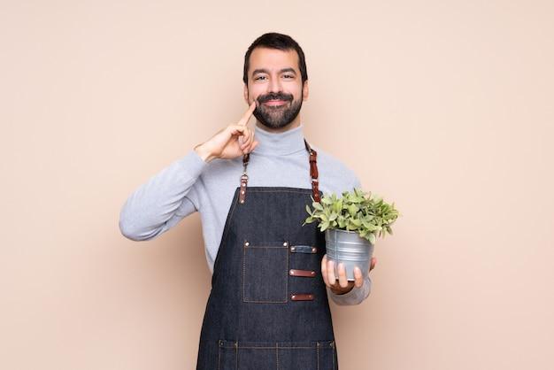 Equipaggi la tenuta della pianta sopra fondo isolato che sorride con un'espressione felice e piacevole