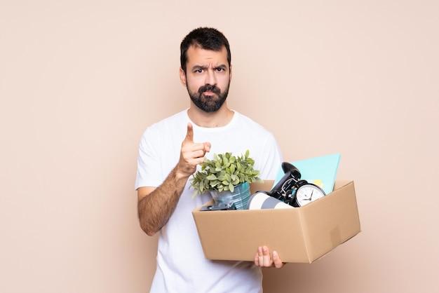 Equipaggi la tenuta della scatola e muoversi nella nuova casa frustrata e indicare la parte anteriore