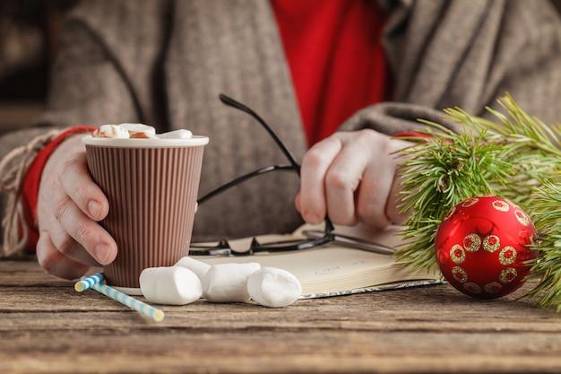 Equipaggi la tenuta della tazza di cacao caldo con le caramelle gommosa e molle, bevanda di natale dell'inverno