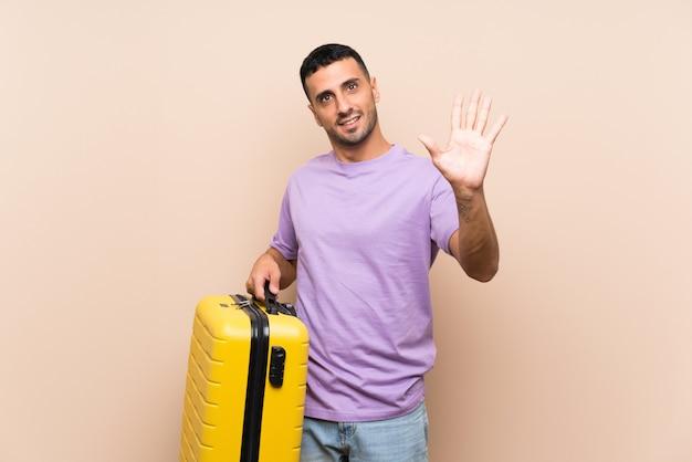 Equipaggi la tenuta della valigia sopra il saluto isolato con la mano con l'espressione felice
