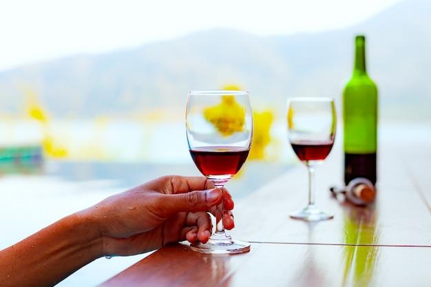Equipaggi la tenuta e la bevuta del vino rosso mentre nuotano e rilassandosi nella piscina