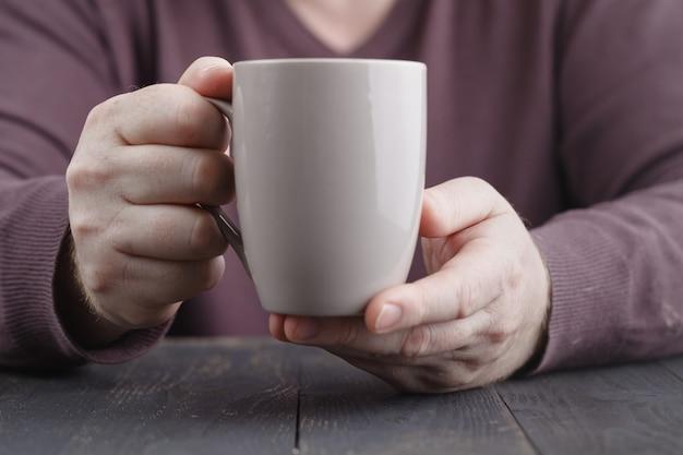 Equipaggi la tenuta in tazza di caffè delle mani su superficie di legno