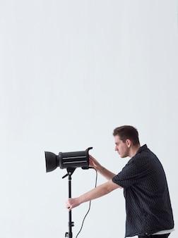 Equipaggi lateralmente il fotografo che guarda attraverso la macchina fotografica e lo spazio della copia
