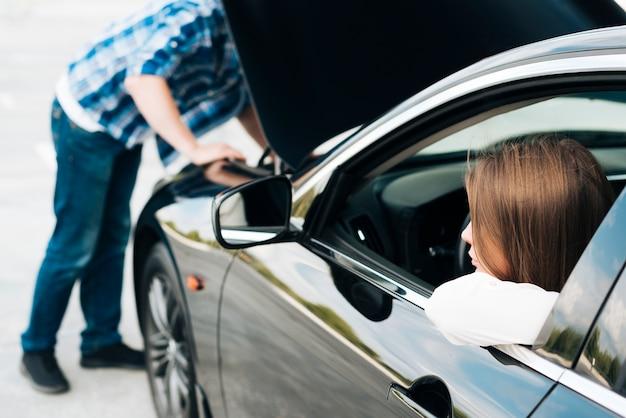 Equipaggi lavorare al motore e alla donna che si siedono in automobile