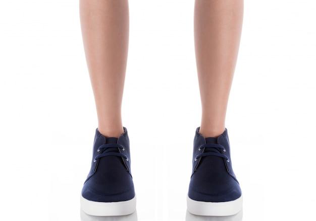 Equipaggi le calzature blu d'uso di modo che stanno con la vista frontale isolata su bianco