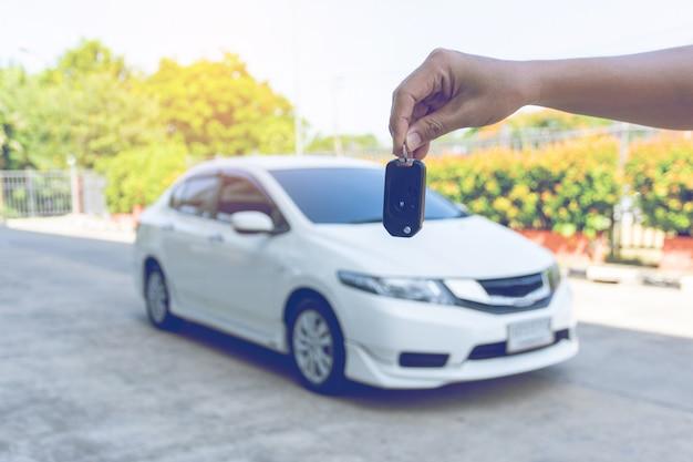 Equipaggi le chiavi della macchina della tenuta con l'automobile sopra