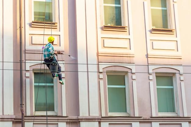 Equipaggi le finestre e la parete di pulizia sulla vecchia città che bulding