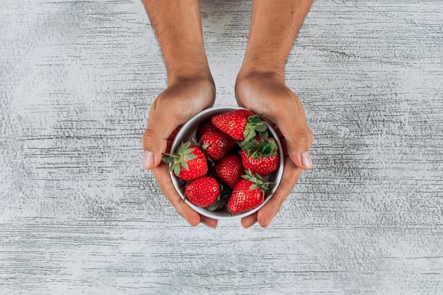 Equipaggi le fragole della tenuta in una ciotola su fondo di legno leggero, vista superiore.