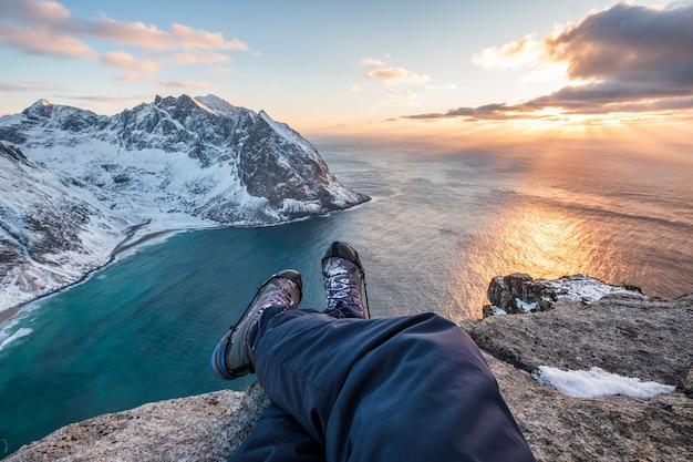 Equipaggi le gambe trasversali della viandante che si siedono sulla montagna di punta con la linea costiera al tramonto