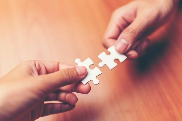 Equipaggi le mani che collegano il pezzo di puzzle delle coppie in ufficio. affari di successo