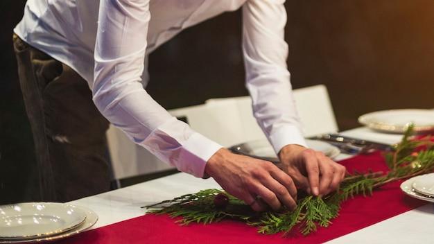 Equipaggi le mani che decorano la tavola con il ramo di albero dell'abete