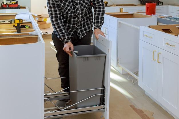 Equipaggi le mani che montano il bidone della spazzatura della mobilia nella cucina