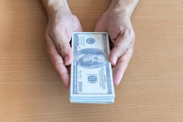Equipaggi le mani che tengono 100 banconote in dollari sulla tavola di legno. ricchezza e concetto finanziario