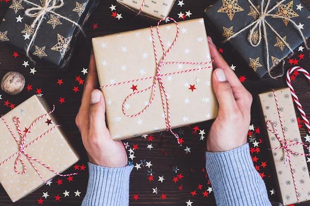 Equipaggi le mani che tengono il contenitore di regalo della festa di natale sulla tavola festiva decorata