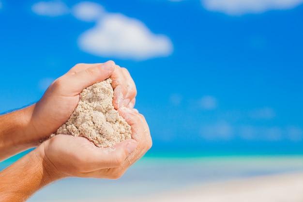 Equipaggi le mani che tengono il fondo tropicale bianco di forma del cuore della forma della spiaggia il mare