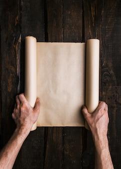 Equipaggi le mani che tengono il vecchio rotolo della carta marrone sul fondo di legno scuro delle plance. concetto minimalista creativo di avventura di viaggio. ricerca del tesoro, ricerca di un modello piatto. spazio per testo, scritte, spazio di copia