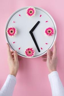 Equipaggi le mani che tengono l'orologio bianco creato dai fiori rosa freschi della gerbera