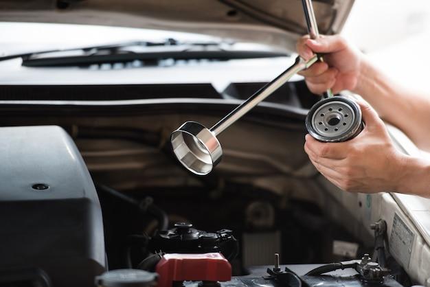 Equipaggi le mani che tengono la chiave del tappo del filtro dell'olio e il filtro dell'olio automobilistico che prepara cambiare.