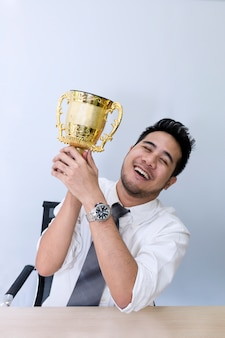 Equipaggi le mani che tengono la tazza dorata, le congratulazioni e il vincitore su successo.