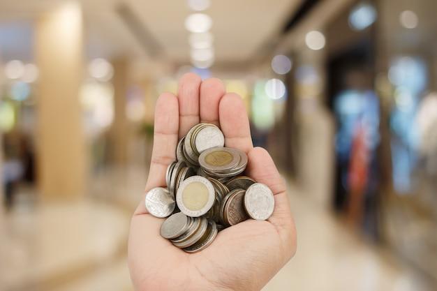 Equipaggi le mani che tengono le monete sopra vaga nel fondo del centro commerciale