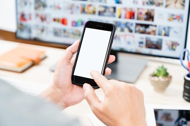 Equipaggi le mani che tengono lo schermo bianco in bianco dello smartphone mobile commovente per derisione su e progettazione di app