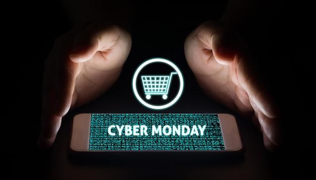 Equipaggi le mani che tengono lo smart phone con testo e carrello cyber lunedì sugli schermi virtuali sullo smartphone.