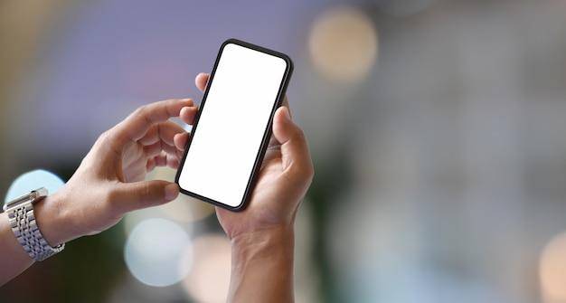 Equipaggi le mani che tengono lo smartphone dello schermo in bianco con bokeh leggero vago