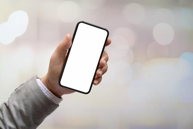 Equipaggi le mani che tengono lo smartphone dello schermo in bianco con fondo vago.