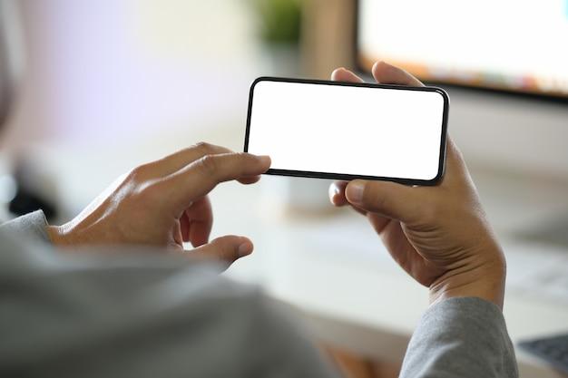 Equipaggi le mani che tengono lo smartphone mobile dello schermo in bianco in ufficio