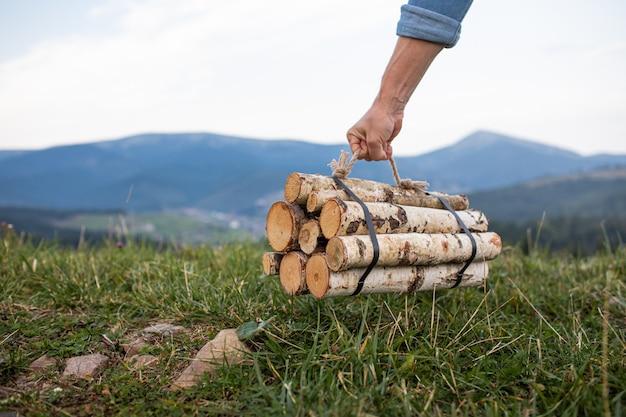 Equipaggi le mani del viaggiatore che tengono la legna da ardere per fuoco in montagne. posto per iscrizione.