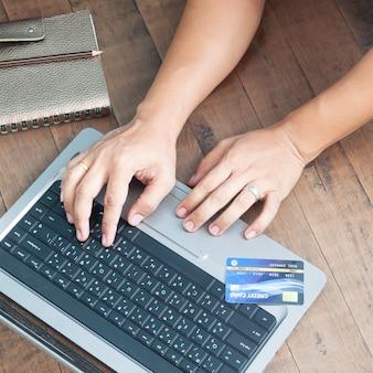 Equipaggi le mani facendo uso del computer portatile e della carta di credito. acquisti online.