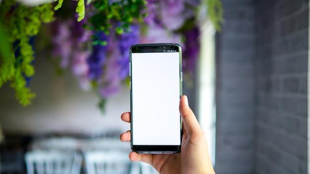 Equipaggi lo schermo bianco dell'esposizione dello smartphone della tenuta per l'app del modello sul fondo della sfuocatura nel decoratio