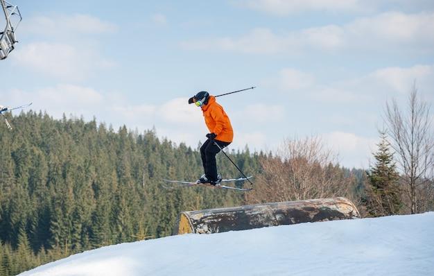 Equipaggi lo sciatore in volo durante il salto sopra un ostacolo