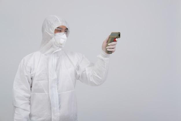 Equipaggi lo scienziato che indossa l'uniforme protettiva biologica, la maschera ed i guanti che misurano la temperatura corporea con il termometro infrarosso della fronte