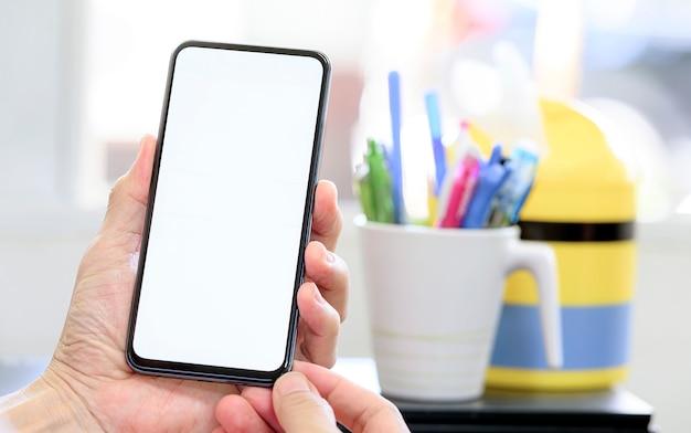Equipaggi lo smartphone della tenuta della mano con lo schermo in bianco, vista del primo piano.