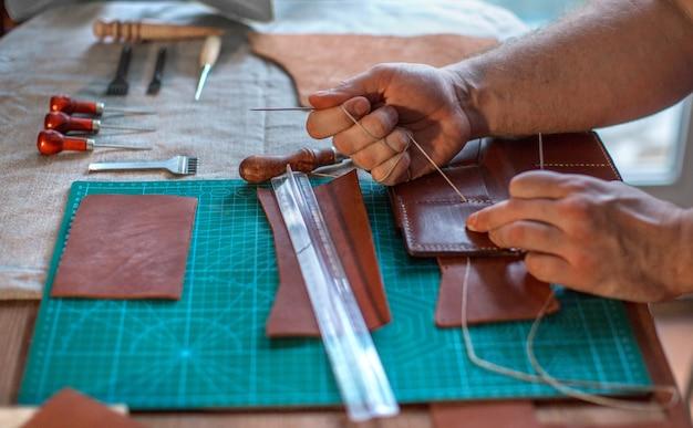 Equipaggi lo strumento di fabbricazione della tenuta e lavorare al pezzo di cuoio