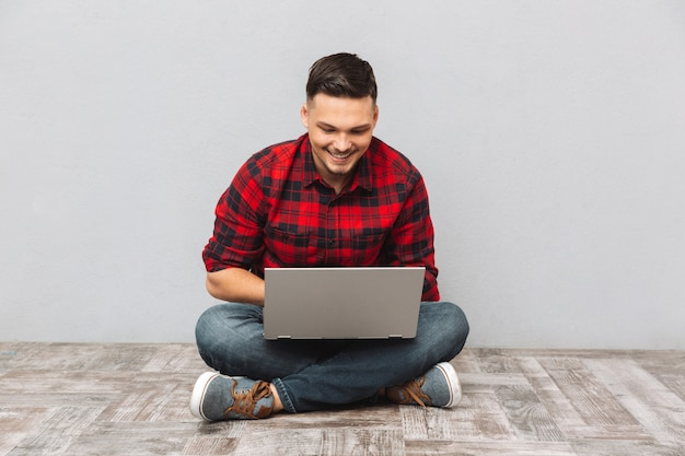Equipaggi lo studente che lavora al computer portatile mentre si siedono sul pavimento