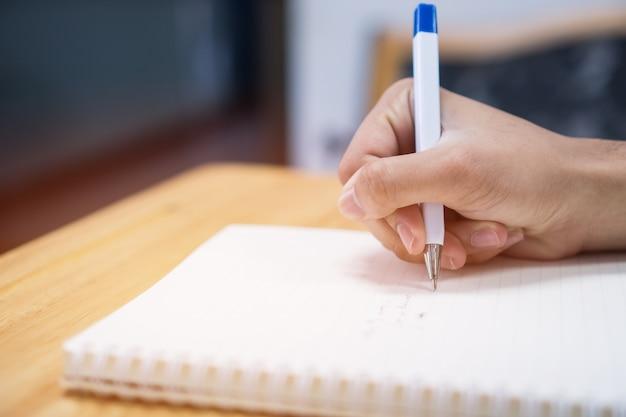 Equipaggi lo studente che prende e che scrive le note sul taccuino con la penna in biblioteca all'università dell'istituto universitario