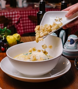Equipaggi mettere il ripieno del pane nella ciotola cremosa della minestra di pollo guarnita con prezzemolo