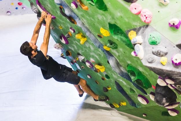 Equipaggi praticare la scalata di roccia sulla parete artificiale all'interno. stile di vita attivo e concetto di bouldering.