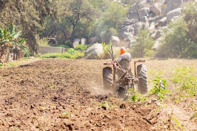 Equipaggi preparare la terra per il raccolto con il trattore sull'azienda agricola