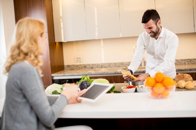 Equipaggi preparare un pasto mentre una giovane donna che si siede e l'uso delle compresse in una cucina moderna