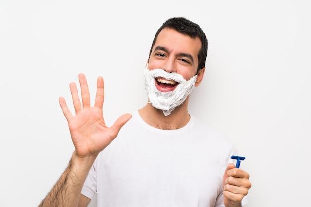 Equipaggi radersi la barba sopra la parete bianca isolata che conta cinque con le dita
