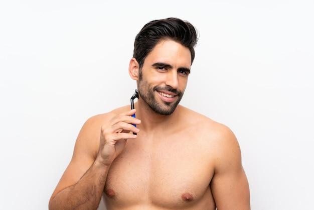 Equipaggi radersi la sua barba sopra la parete bianca isolata