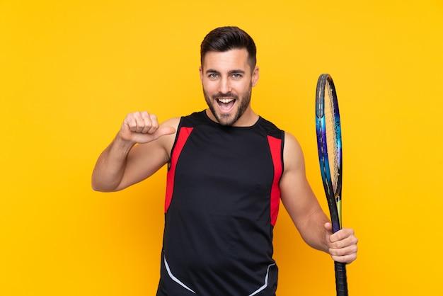 Equipaggi sopra la parete gialla isolata che gioca a tennis e fiero di se stesso