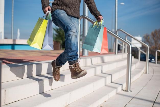 Equipaggi uscire da un centro commerciale con i sacchetti della spesa variopinti