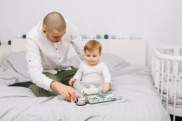 Equipaggi vicino al piccolo bambino che gioca con il giocattolo sul letto
