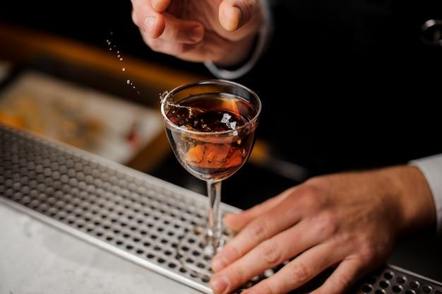 Equipaggia la mano che tiene un bicchiere con spruzzi di bevanda alcolica con una fetta di arancia